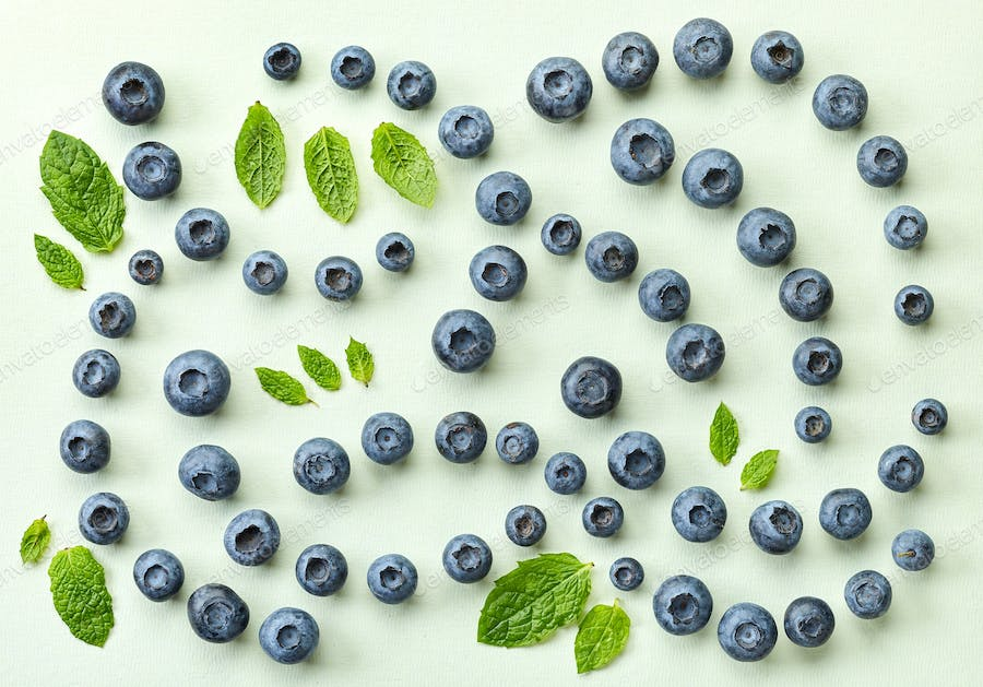 fresh blueberries on light green paper background