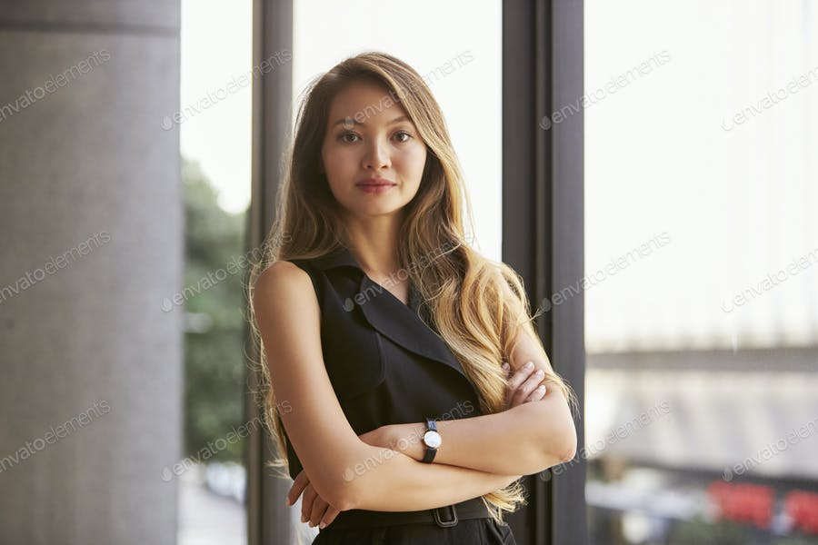 Confident young Asian businesswoman, waist up, close up