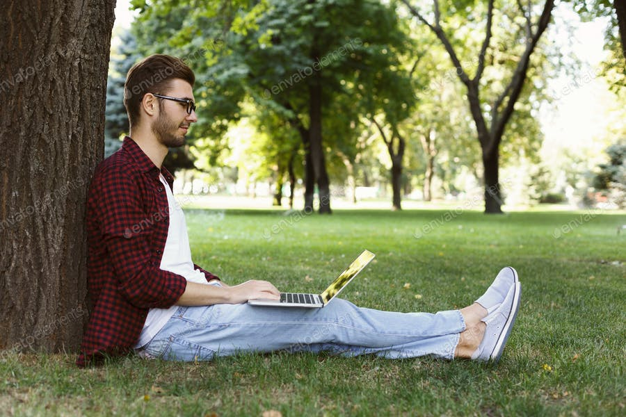Man sitting on grass with laptop outdoors