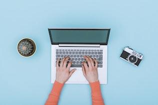 Minimalist light blue workspace with laptop