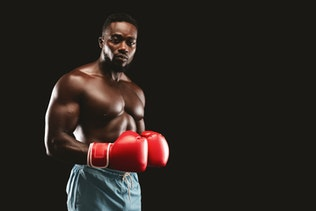 Athletic fighter with red gloves on posing over black background