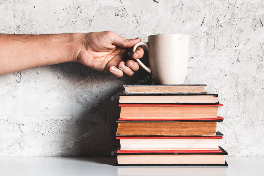 A man takes coffee from a stack of books. Education, learning, reading, hobbies