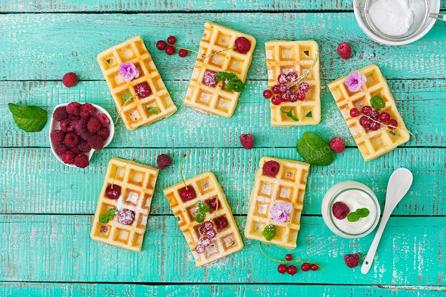 Belgium waffles with raspberries and yogurt on wooden table. Flat lay. Top view