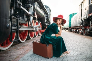 Woman in red hat against vintage steam train